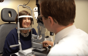 Dr. Drees conducts an eye exam on a happy and comfortable patient